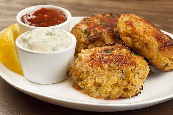 Our take on traditional, Maryland-style crab cakes seasoned with Old Bay and served with easy-to-make versions of both tartar and cocktail sauce.
