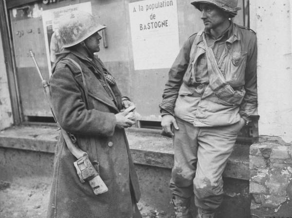 Exhausted US infantryman (L-R) Adam H. Davis & Milford A. Sillars of 110th Reg., part of 'Team SNAFU' (a patch force aiding in the defence of Bastogne) taking a break during 8-day German siege.