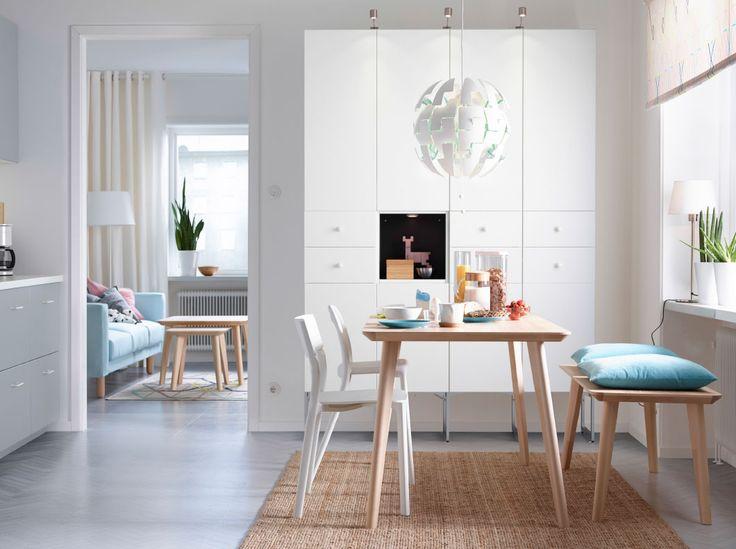 Salle à manger claire avec table en frêne pouvant accueillir quatre personnes. Un banc en frêne et deux chaises blanches complètent l'ensemble.