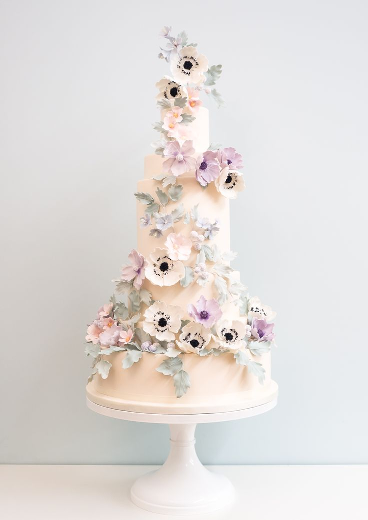 This stunning cake was created by @rosalindmiller and features intricate detailed pastel pink, purple and yellow flowers woven around a cone shaped cake, with realistic pretty leaves.