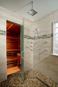 This Contemporary spa bath features a chrome Kohler ceiling mounted rain shower head, handheld, and multiple body sprays.  This Wayne, PA bathroom also features a walk in sauna separated by a frosted glass door for a true spa experience.