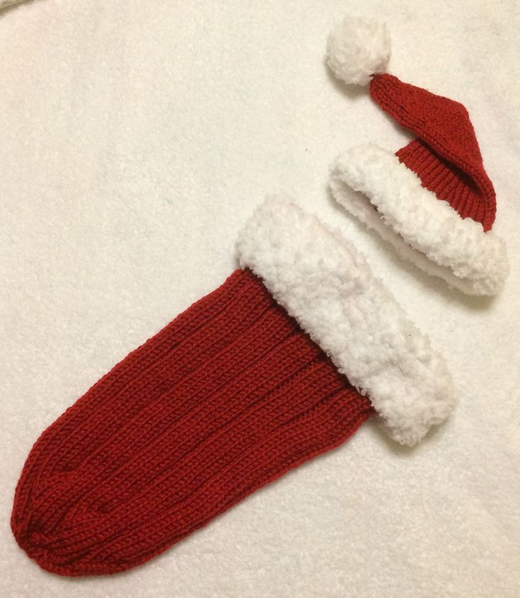 Free Knitting Pattern for Santa Baby Cocoon - This holiday set includes baby Santa hat and snuggle sack. It's great for holiday photos for a new arrival, and will fit most babies from newborn up to 3-6 months.Designed by Danielle Lanois