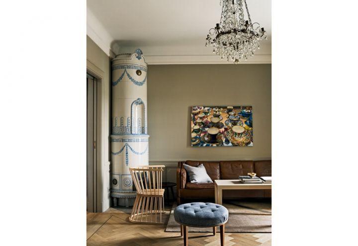 Un'antica stufa svedese in maiolica di stile Gustaviano domina una delle 12 camere dell'hotel. Divano vintage di Børge Mogensen, tipica sedia inglese da giardino in legno, Flip di Howe® e tavolo su disegno Studioilse