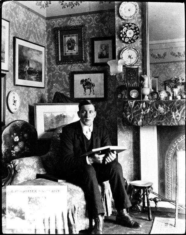 """This photograph shows an interior in a middle-class British home in 1911. Although the photograph was taken after 1910, the room shows many late Victorian features. The walls are covered with pictures and decorative plates, and the fireplace has a mantleboard drapery."""