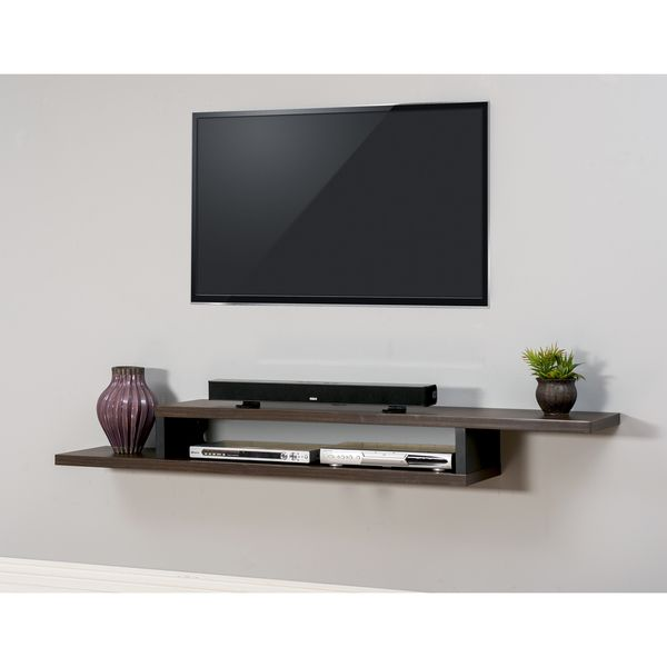 Engineered using an asymmetrical design, this wall mounted TV console has a modern flair with the appearance of a floating shelf. Finished in a Columbian Walnut wood tone with black accents, this bold