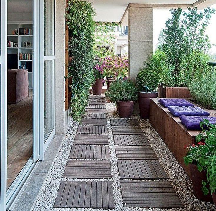 Терраса в многоэтажном доме. Зелень, гравий, деревянные дорожки и скамья с подушками создают нужную атмосферу.