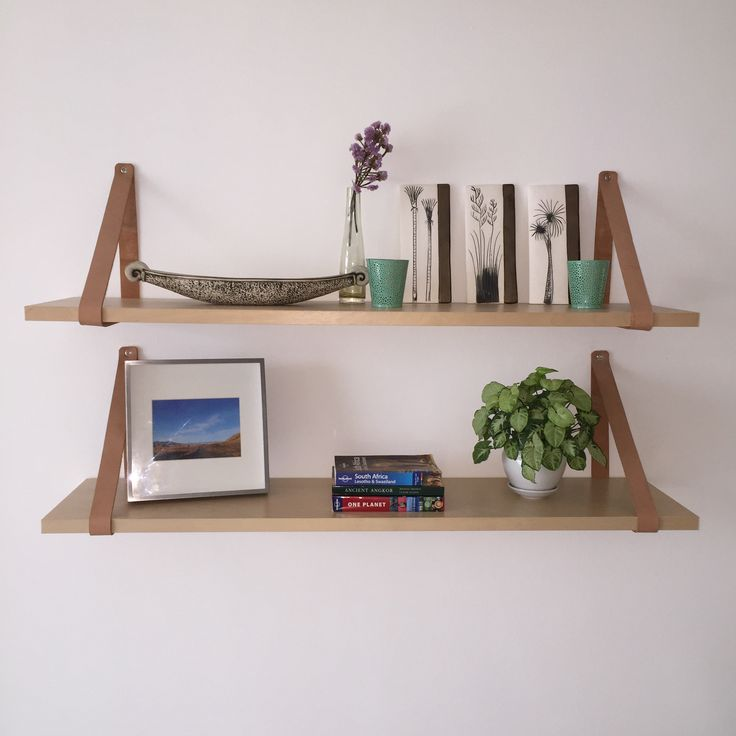 Floating wooden shelves with leather straps.