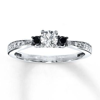 A brilliant round white diamond is graced on either side by a dramatic round black diamond in this remarkable diamond engagement ring for her. Additional white diamonds decorate the 10K white gold band. The ring has a total diamond weight of 3/8 carat. Black Diamonds are treated to permanently create the intense black color.  and $849