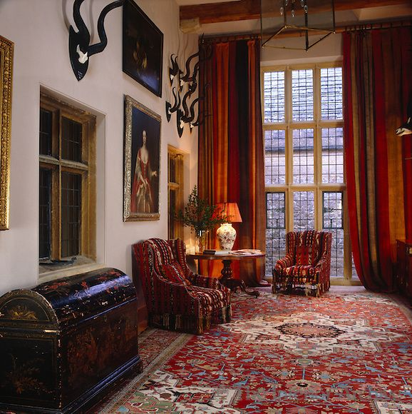 Robert Kime ~ The double-height entrance hall is richly furnished with heavy striped curtains against the window