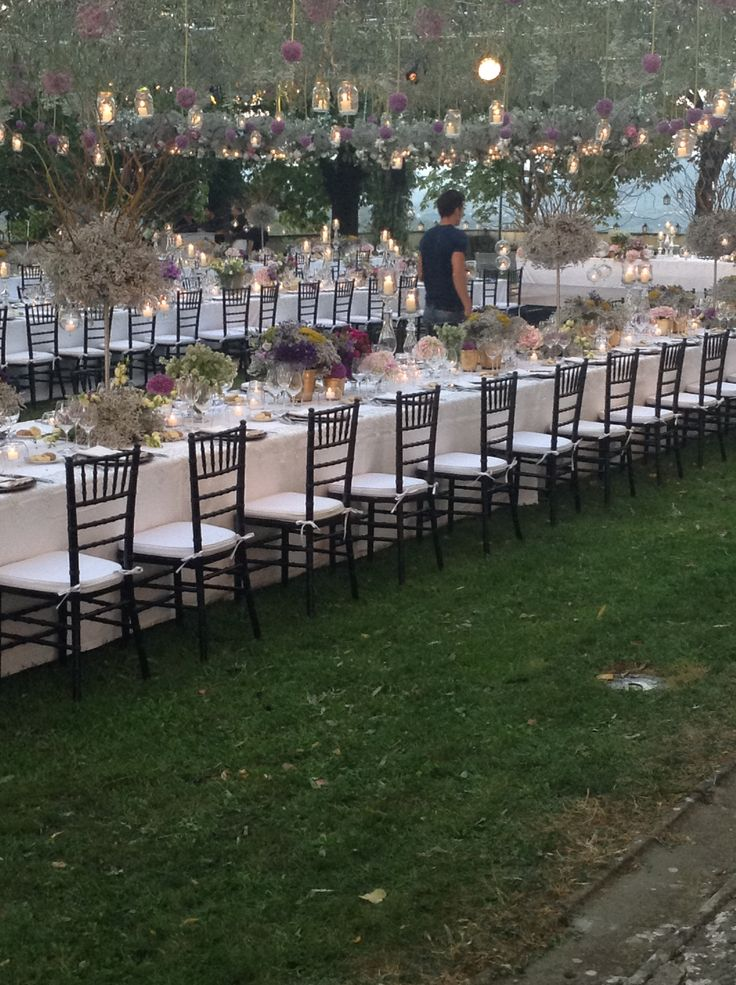 Table set up with flowers, ceiling decorated with greenery, flowers and hanging glass jars with tea light candles
