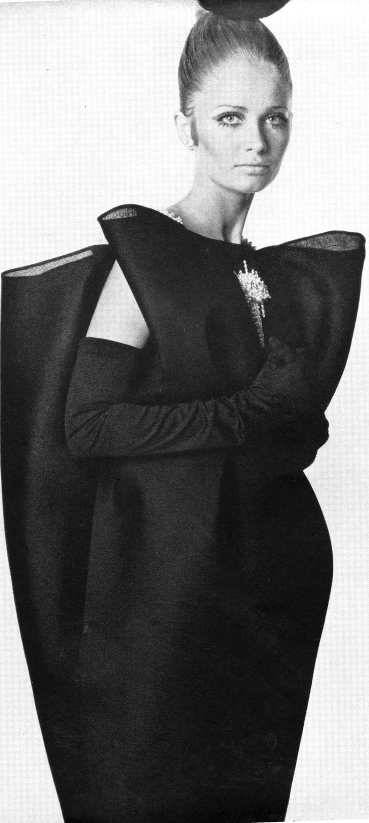 "A Balenciaga dress of black gazar, ""suspended like butterflies in mid-air on diamanté straps and drawn close towards the knee,"" as described by Vogue. The 'wings' are indented with a single diamanté jewel. Photo from Vogue, September 1967."