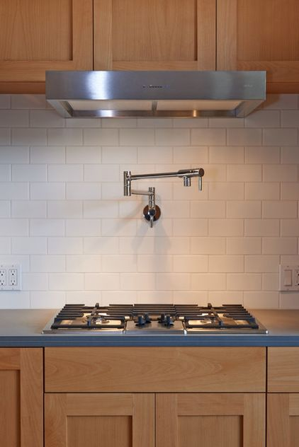 The four-burner gas cooktop has a streamlined vent hood above, with a clean look that doesn't overpower the kitchen.   Cooktop: Bosch; pot filler: Moen; vent hood: Zephyr