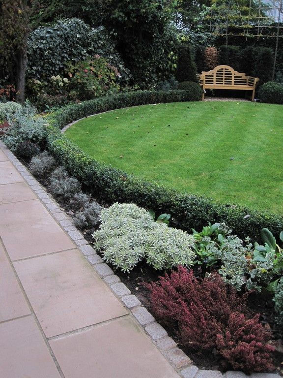 the box edged circular lawn of this garden in golders green london maximises