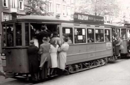 "1943. ""Tramtrossen"" on tram line 23 at the Overtoom in Amsterdam. Due to limited availability of tram wagons during the German occupation and also in 1945 after the occupation had ended ""tramtrossen"" occurred daily at rush hour. #amsterdam #1943 #Overtoom"