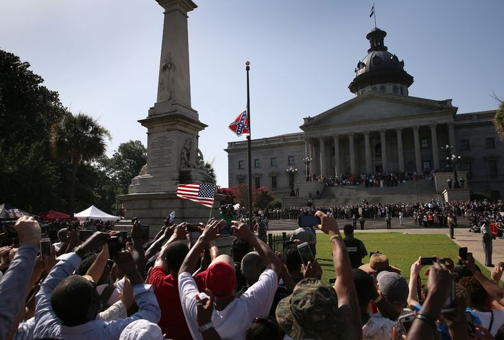 A crowd cheers as a South Carolina state police honor guard lowers the Confederate flag from the Statehouse grounds on July 10, 2015 in Columbia, South Carolina.