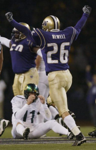 Quarterback Kellen Clemens of the University of Oregon Ducks slowly gets up after being sacked as Jimmy Newell of the University of Washington...