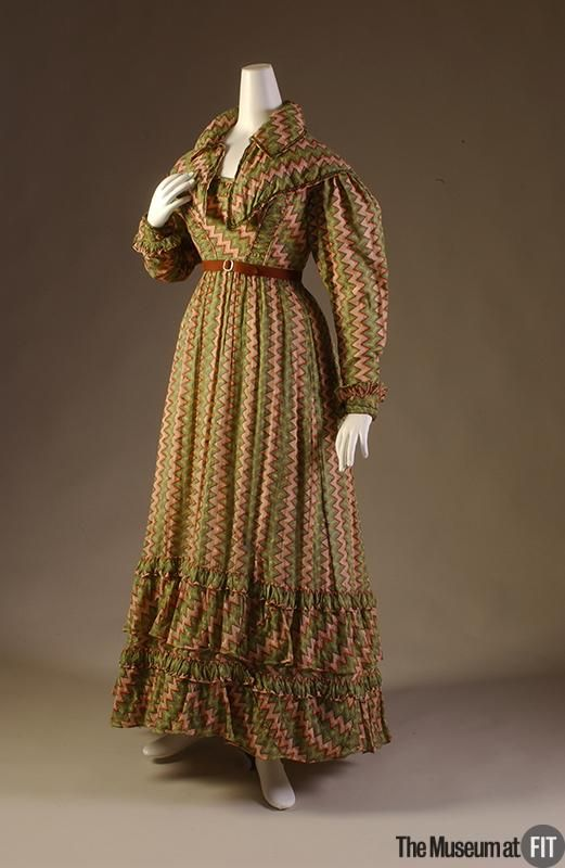 """1820-1822 Dress of multicolor cotton and green wool braid, England, FIT Collection """"By the 1820s, multicolor, patterned garments had begun to replace the gossamer white of the century's first decade, due in large part to new developments in printing technology. Textile manufacturers were able to me..."""