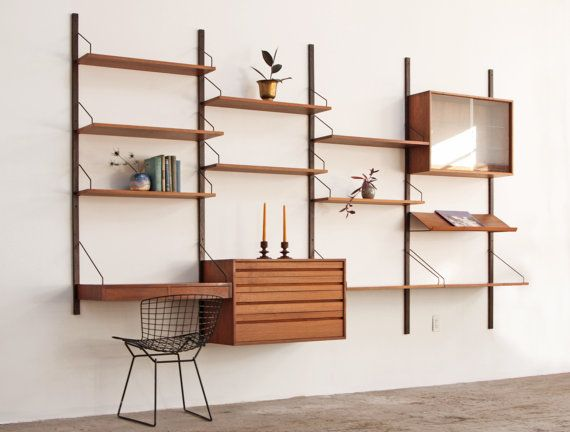 Four bay Danish wall unit designed by Poul Cadovius. Five wood rails that suspend two cabinets, 9 shelves a desk with drawers and a book /