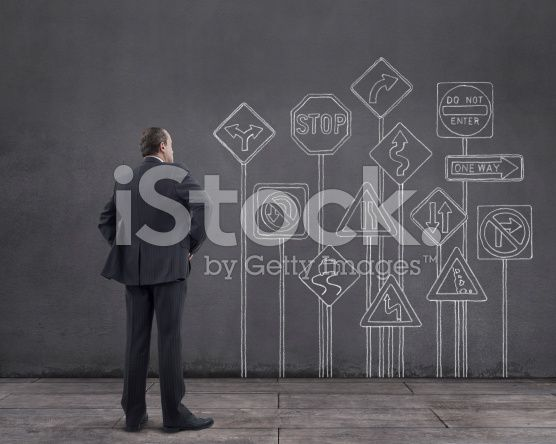 Businessman with Road Signs Sketched on the Wall (royalty-free stock photo) © mgkaya
