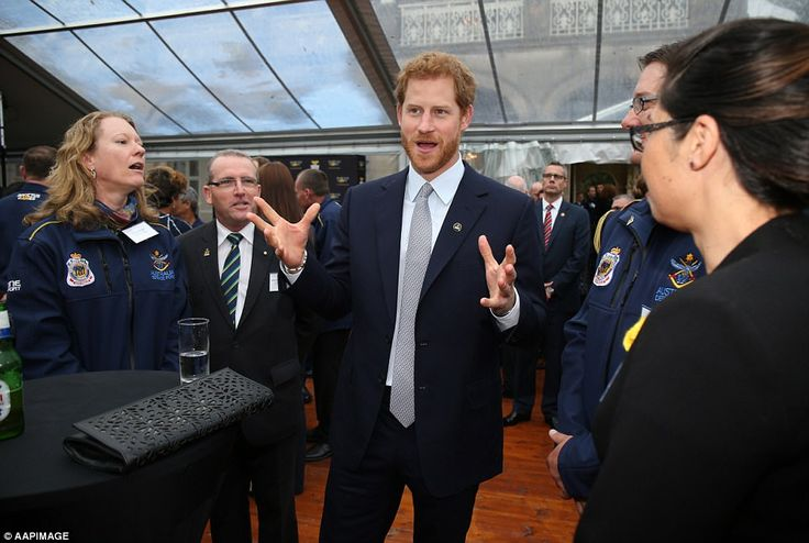 Prince Harry appears to be engaged in animated conversation with fellow guests at the even...