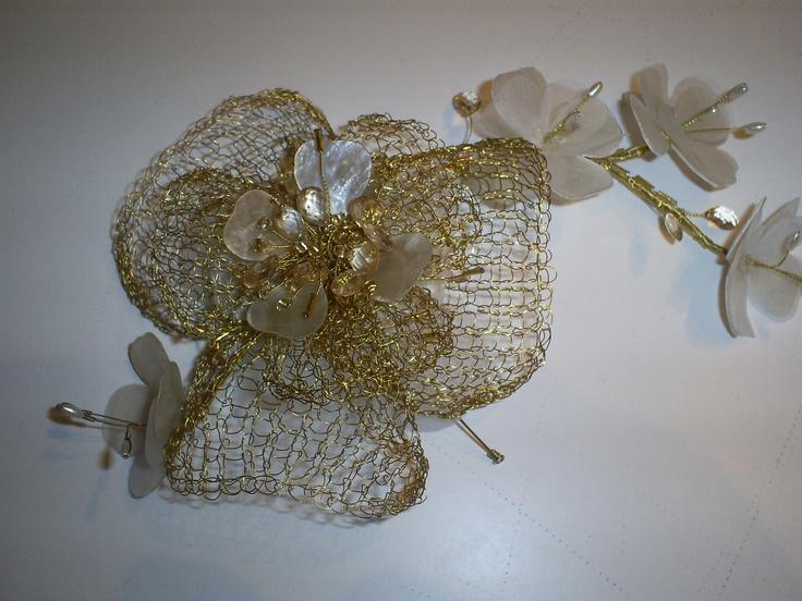 Flor  tejida  en alambre dorado con aplicaciones  de  cristales y nácar.