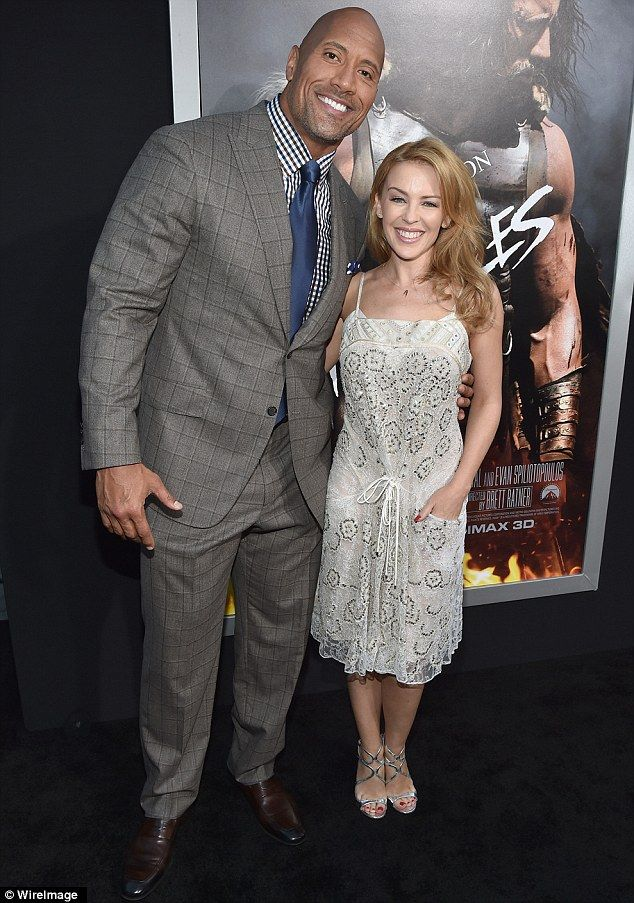 He's a demigod! Even a pair of heels couldn't raise the 46-year-old Australian up to Dwayne 'The Rock' Johnson's height