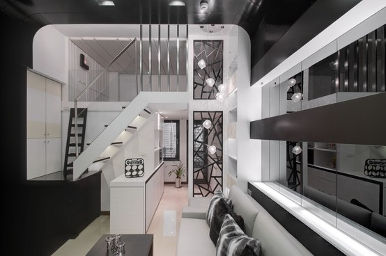 利用塑鋁板營造冷冽的科技感,並用灰鏡擴大空間感,拉長沙發背牆的造型延伸至天花板,讓挑高的感覺更加明顯。 並再延續至電視牆,讓空間連結在一起。