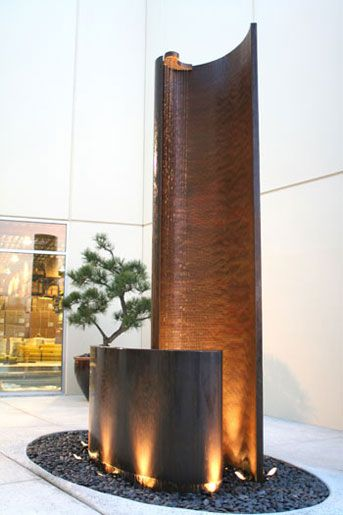 Water Fall Fountain Sculpture with rain curtain in a courtyard,  location is in City of Industry, CA   made from - Ridged and smooth copper with bronze patina