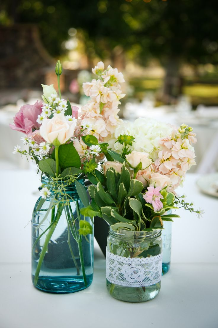 Country wedding table flowers. turquoise mason jars and handmade lace jars.  Peach, ivory and pink table arrangements