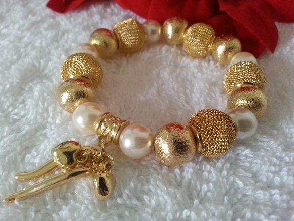 Pulseira confeccionada em fio de silicone com pérolas 10mm, bolas douradas 12mm, bolas vazada douradas 14mm, canequinha, pingentes pimentinha e coraçõezinhos também dourados.