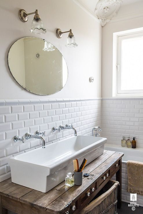 Amazing bathroom features off white paint on upper walls and beveled subway tiles on lower walls framing vintage glass sconces illuminating an oval frameless mirror over a reclaimed wood washstand topped with white porcelain trough sink paired with his and her wall-mounted faucets beside a tiled drop-in tub accented with white beveled subway tile surround and vintage shower kit.