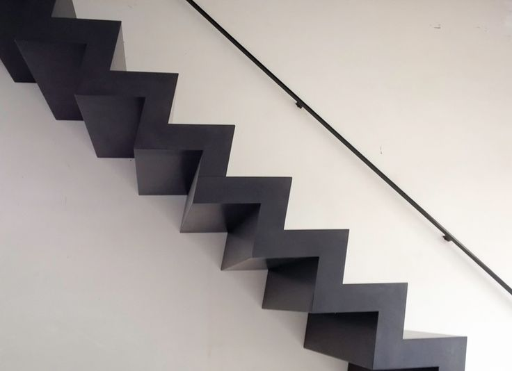 Zwarte z trap op maat in Brut staal met strakke leuning tegen de muur