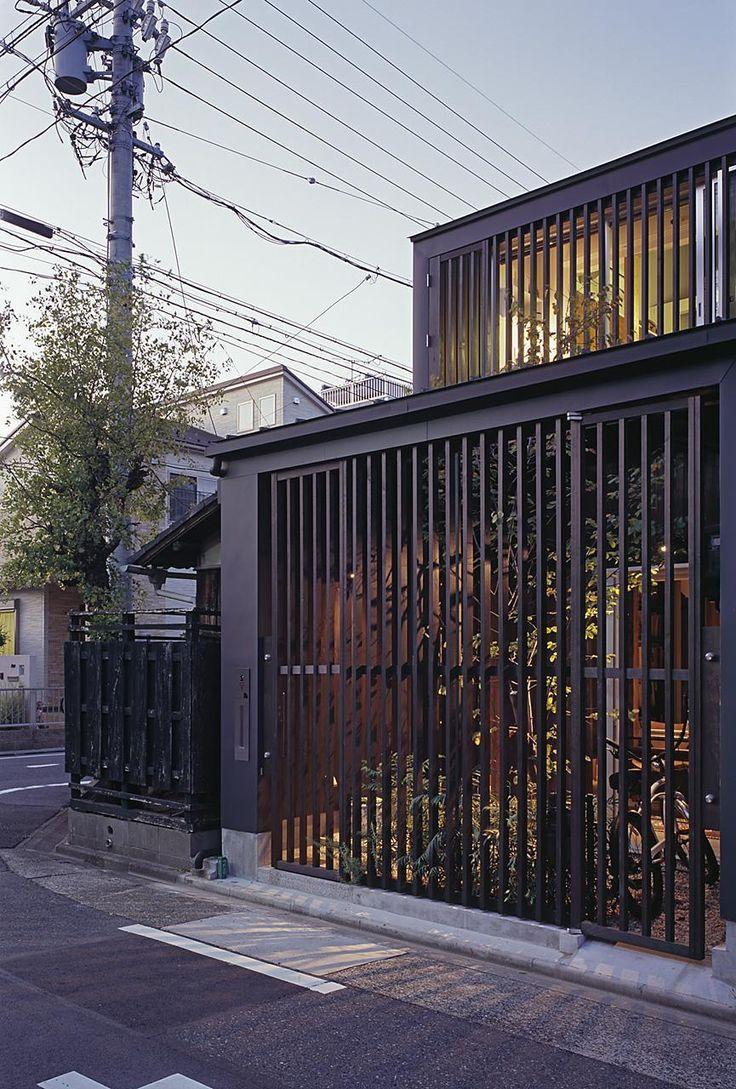 門扉の格子を閉じると一面の格子が趣を増す。<br /> 前庭の緑が格子からのぞく様子は街に潤いをつくる。 専門家:向井一規が手掛けた、外観夕景(東から)(『再生M』~通り土間のある町屋のリノベーション~(古民家再生))の詳細ページ。新築戸建、リフォーム、リノベーションの事例多数、SUVACO(スバコ)