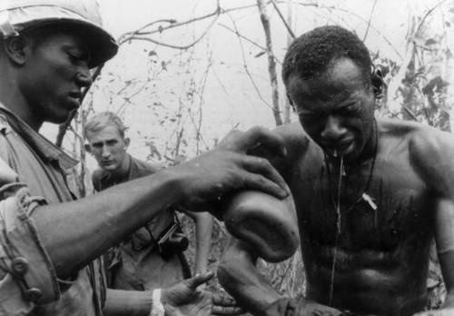 Medic Green pours water on Staff Sgt. Gaines as Gaines emerges from a VC Tunnel, Vietnam War  Keystone / Getty Images