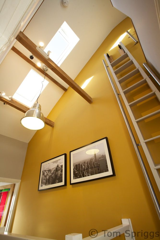 Innovative use of pull-out ladder to access mezzanine style loft conversion gives masses of daylight into Victorian terrace in Exeter, Devon. Farrow and Ball India Yellow ties all the spaces together. Tom Spriggs Architect ltd.