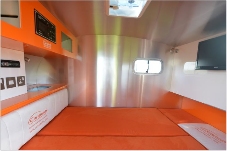 The interior of the pod showing the mattress made into a bed but also forms a sofa either on the side wall you see or against the head board.