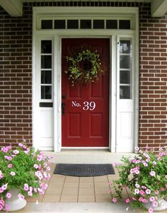 This charming front porch has a door mat, perennials potted in white urns, and the house number boldly placed on the center of the door in a contrasting white.