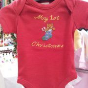 $14.95      My First Christmas  Size 0000  This bright red onesie is the perfect outfit for the big day (or even the lead up – you only get one right!) It features a cute little teddy peeking out of a bright blue and green stocking.  The design can be done in different sizes and colours. Just one example of the soon to be released 'My First' range.