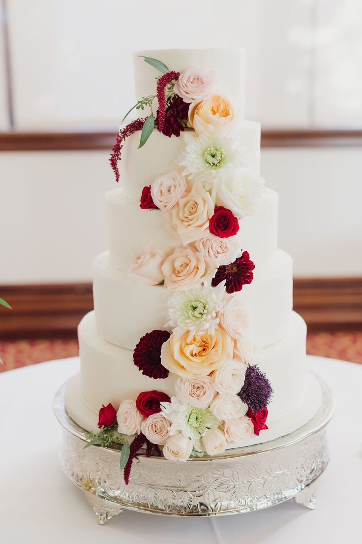 Tall wedding cake, cascading colorful roses, elegant silver cake stand, repin to your own inspiration board // Stacy Able Photography