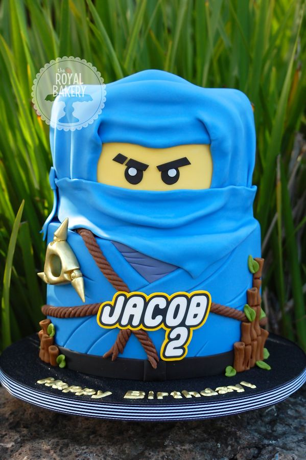"""My customer gave me a photo by jbarrett573 and asked me to copy it in blue. I added a few extra details, but the original design is all hers. Thank you! Jacob's name is an edible image. The cake is 8"""" and 7"""" and is covered in FondX Elite American Blue. The draping of the hood was really hard (I did each piece five times), but the rest of the cake was really fun to do."""