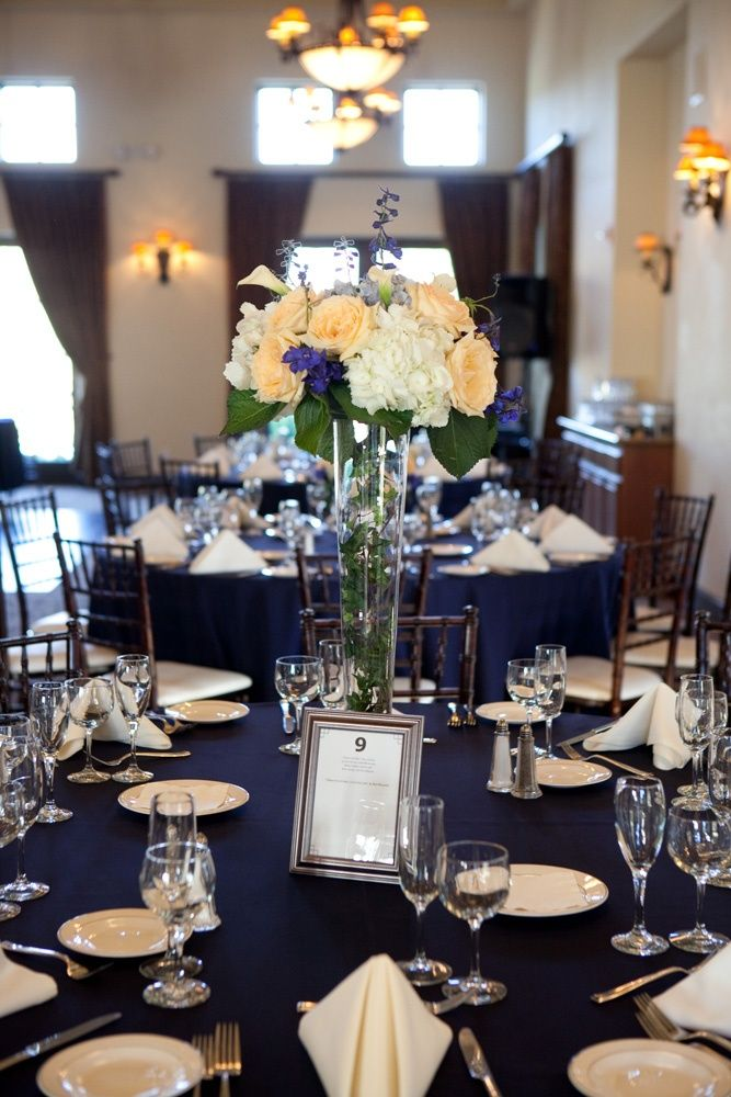 Blue linens with white napkins, but no chair covers. You can also imagine the yellowish roses replaced by red ones.