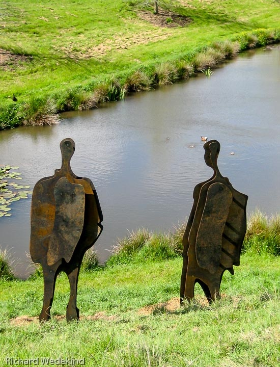 Conversation Piece: Two corten steel figures by the pond at Brick Bay Sculpture Trail, Warkworth. Private collection.