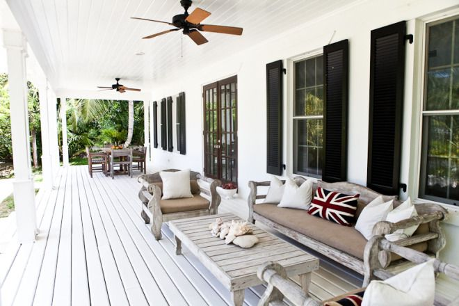 porch, white paint, black shutters, ceiling fans, neutral furniture, french doors, union jack pillows...could do a lot of outdoor living in this space