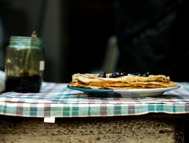 Stack of clătite (Romanian crêpes) with sour cherries.