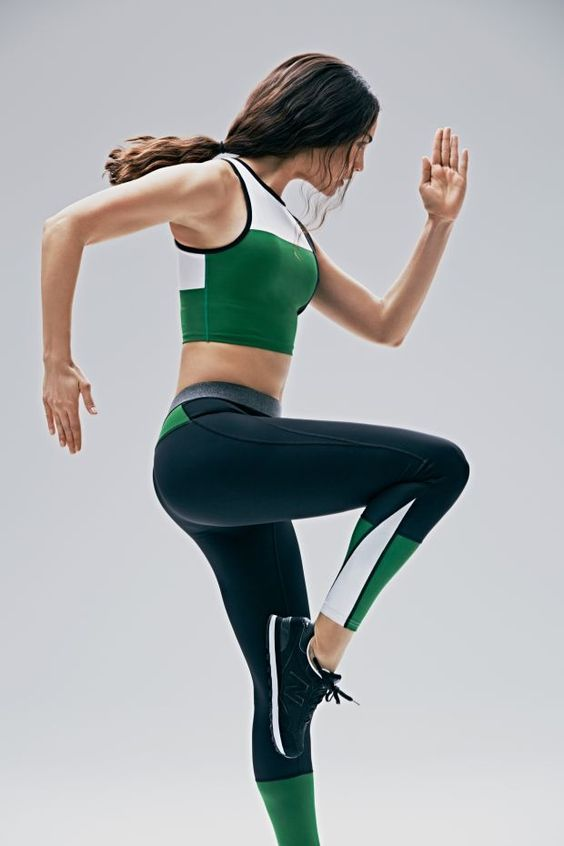 Lightly tanned chocolette in emerald crop tank w/ snowy upper, navy trim on arm & neck holes; navy yoga pants w/ emerald shins, calves, upper glutes plus snow blades on ouder calves; snowy-soled navy runners