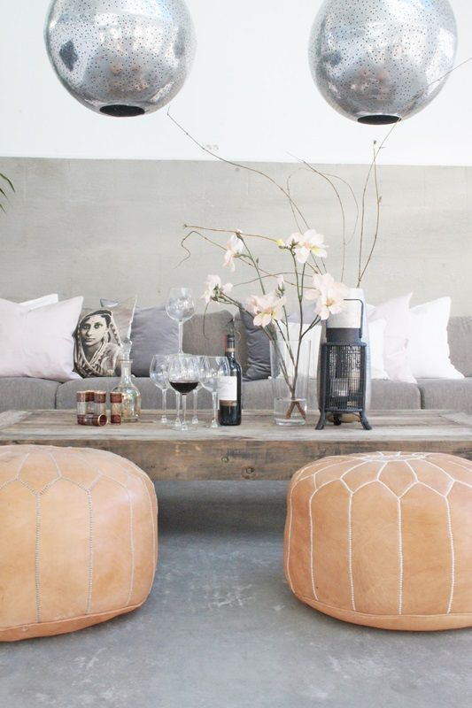 poufs, concrete wall, metallic lamps and wood table. I like it!