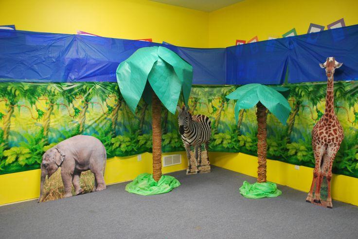 Jungle Jaunt décor. Pool noodle trees, cut out animals, plastic backdrop and blue plastic table cloths.