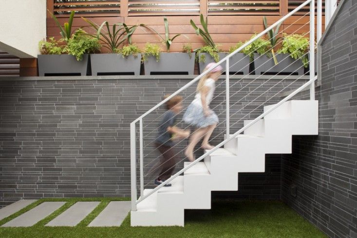White painted steel staircase, artificial turf, Bluestone pavers, gray planters by Loll Designs, Carport by Jeff King, San Francisco | Garde...