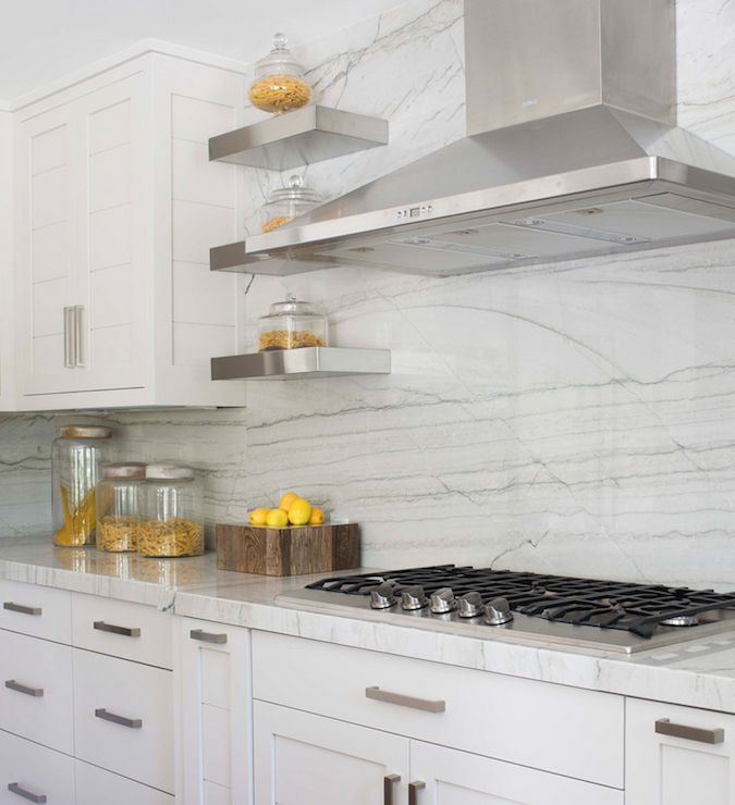Beautiful kitchen features a stainless steel hood flanked by stacked small stainless steel ...