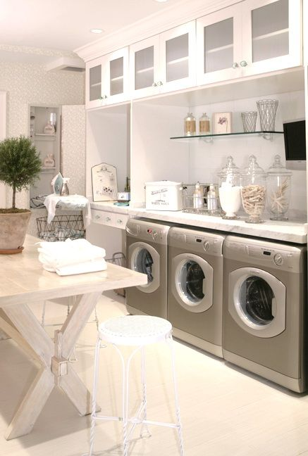Laundry room par excellence Tables for folding, and cabinets for storage, these…